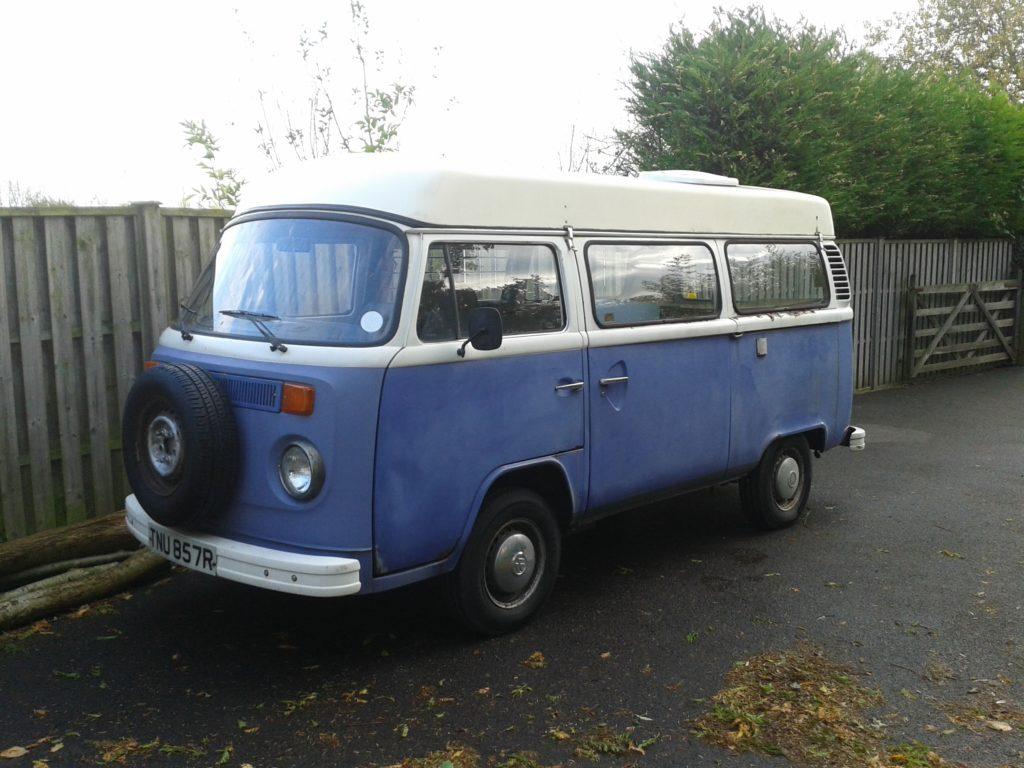 Rusty VW camper van sitting in driveway